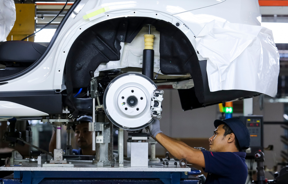 Worker assembles cars at automobile assembly line production plant.