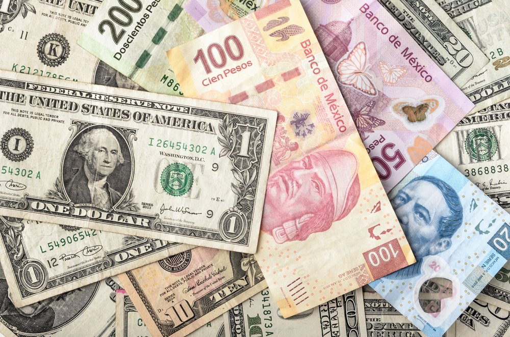 Dollars and Mexican Pesos assorted bills symbolizing gap in wages in Mexico vs. USA